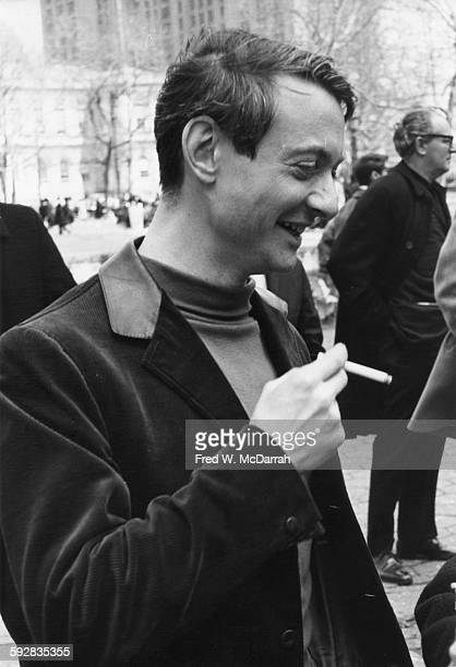 American Pop artist Roy Lichtenstein smokes a cigarette as he attends the March on City Hall to Save Artists Lofts New York New York April 3 1964