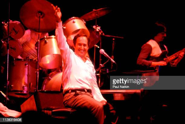 American Pop musician Neil Sedaka plays piano as he performs onstage at the Park West, Chicago, Illinois, November 25, 1978.