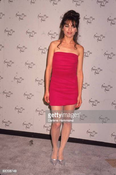 American pop musician Susanna Hoffs wearing a short red dress silver high heels and matching stockings poses in front a wall emblazed with the logo...