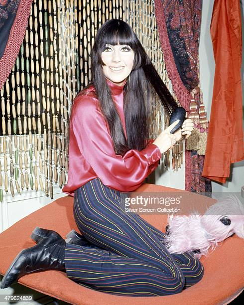 American pop singer and actress Cher brushing her hair, circa 1968.