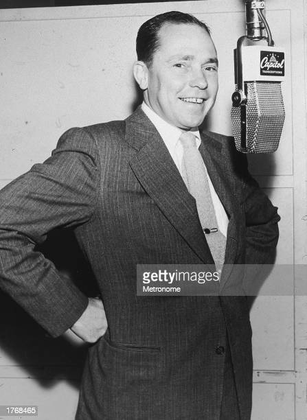 American pop singer and songwriter Johnny Mercer stands behind a microphone in a Capitol Records recording booth c 1950