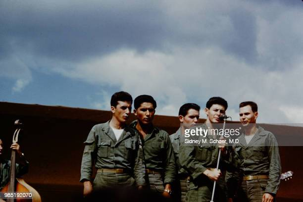 American Pop singer Eddie Fisher , with a backing quartet, performs onstage for troops at the 8063rd MASH , South Korea, January 1952. The vocalists...