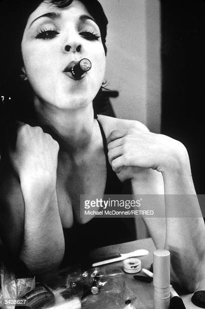 American pop singer Madonna leaning on a vanity table with a lipstick tube in her mouth as if it were a cigar New York City She has short dark hair