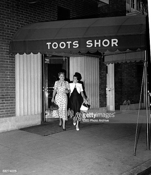 American pop singer Margaret Whiting and Gertrude Greer walk underneath the awning outside Toots Shor's restaurant in New York New York August 9 1949