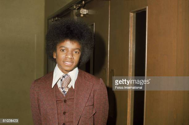 American pop singer Michael Jackson wears a brown suit standing backstage at an event January 19 1974