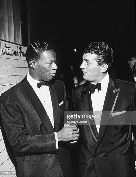 American pop singer Nat King Cole chats with American singer and actor Dean Martin , while attending the premiere of director Edward Dmytryk's film,...