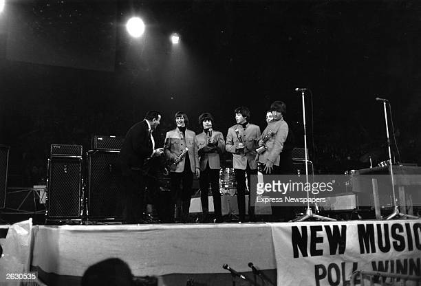 American pop singer Tony Bennett presents an award to The Beatles at the New Musical Express Poll Winners' Concert at Wembley London