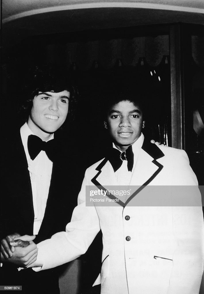 American pop singers Donny Osmond (left) and Michael Jackson shake hands and smile as they meet before acting as hosts of the first ever American Music Awards in Hollywood, California, February 19, 1974.
