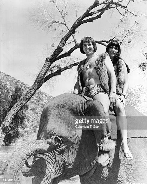 1967 American pop singing duo Sonny Bono and Cher sit atop an elephant dressed in prehistoric caveman and cavewoman attire in a promotional still for...