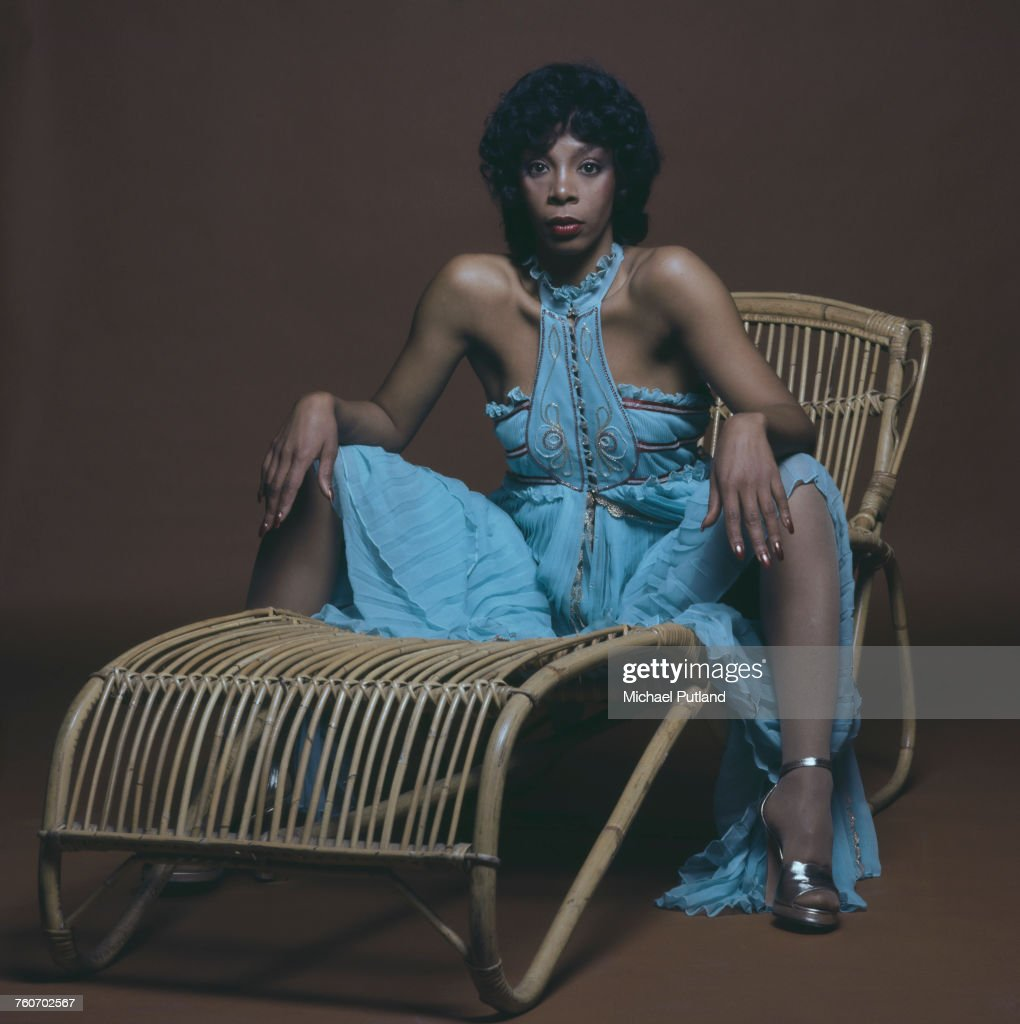 American pop, soul and disco singer and songwriter, Donna Summer (1948 - 2012) posed sitting on a cane lounger chair wearing a long blue summer dress, London, 29th April 1976.