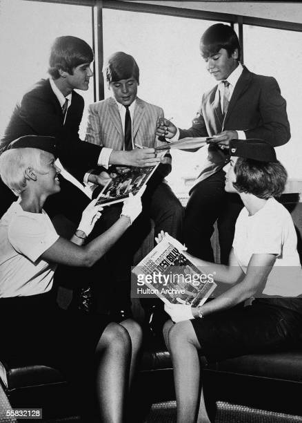 American pop trio Dino Desi and Billy autograph their record covers for two TWA ground hostesses mid to late 1960s From left on the top row Dino...
