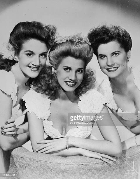 American pop vocal group The Andrews Sisters lean in towards each other in matching dresses in a promotional portrait for their CBS radio program...
