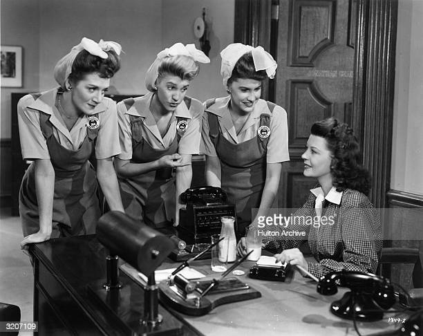 American pop vocal group the Andrews Sisters lean over a desk as they talk with American actor Harriet Hilliard in a still from director Edward F...