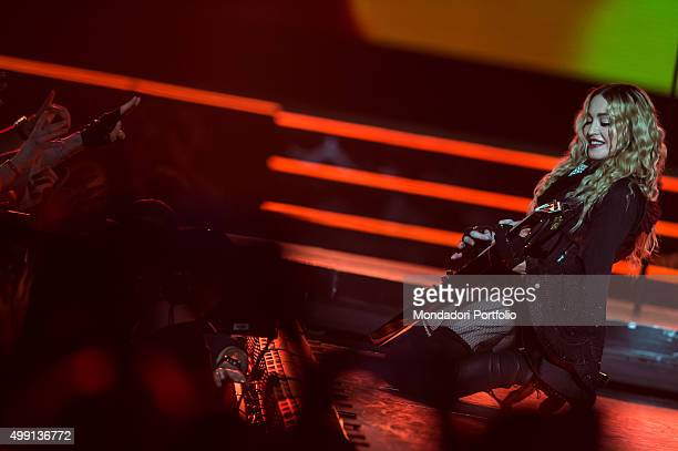 American popstar Madonna in a revealing black dress playing a guitar on her knees in front of some fans during her concert of 'Rebel Heart Tour' at...