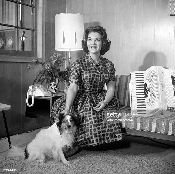 American popular singer Connie Francis sits on a couch and poses at home beside her pet dog and an accordion for an episode of the CBS celebrity...