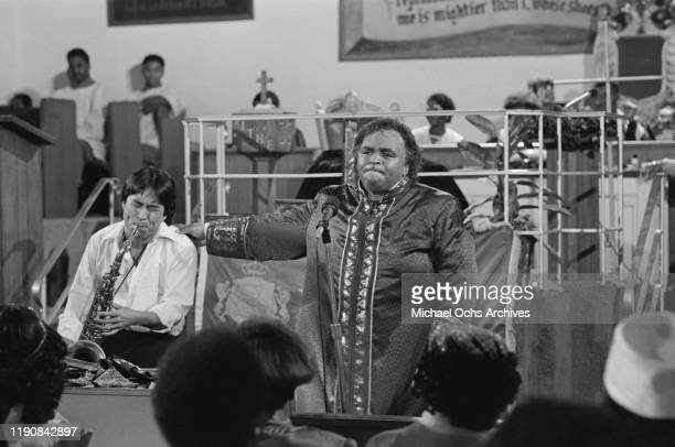 American preacher and singer Solomon Burke is accompanied by a saxophonist during a church appearance, USA, circa 1968.