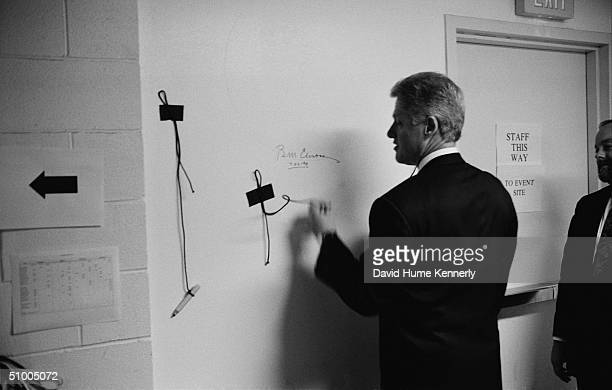 American President Bill Clinton signs a wall while an unidentified man watches Washington DC 1998