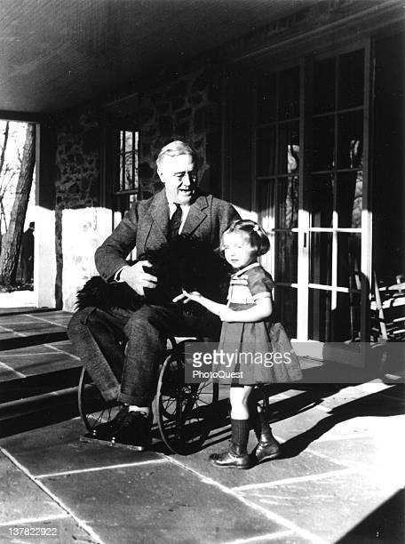 American President Franklin D Roosevelt poses with his dog Fala and a young girl named Ruthie Bie on the porch at Top Cottage Hyde Park New York...