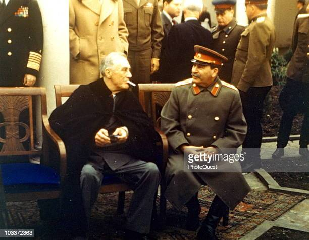 American President Franklin Delano Roosevelt lights a cigarette as he speaks with Soviet General Secretary Joseph Stalin during a break in a photoop...