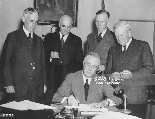 American President Franklin Delano Roosevelt signs the Conscription Bill at the White House Gathered around him are Secretary of War Henry Stimson...