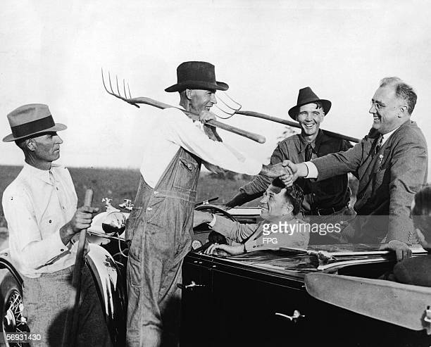 American President Franklin Delano Roosevelt sits in his car and shakes hands with a group of pitchfork carrying farmers, near Warm Springs, Georgia,...