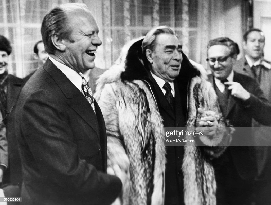 American President Gerald Ford shakes hands with USSR Communist Party Chief Leonid Brezhnev, who is wearing the American President's fur parka. Henry Kissinger is visible behind the two leaders at the meeting in Vladivostok.