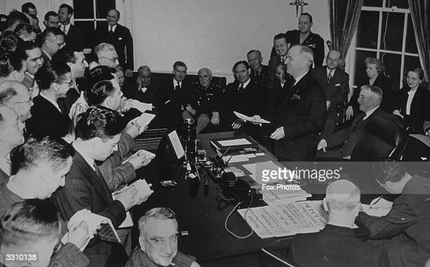 American President Harry S Truman reading the text of his announcement of the unconditional surrender of Germany to news reporters a few minutes...