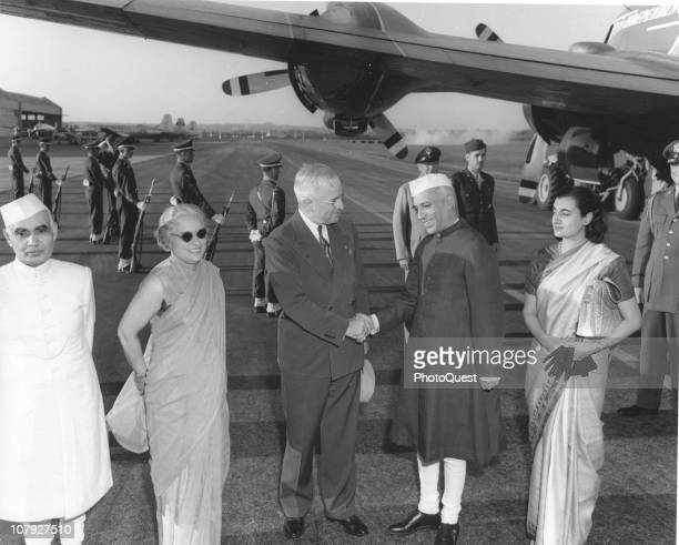 American President Harry S Truman shakes hands with Indian Prime Minister Jawaharlal Nehru on the tarmac as Nehru's sister diplomat Vijaya Pandit and...