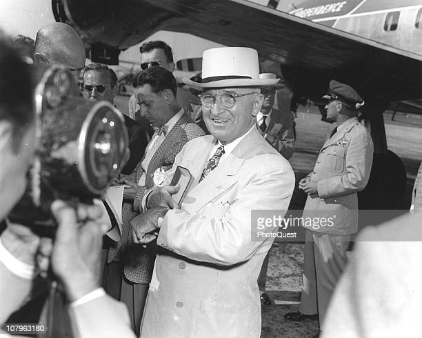 American President Harry S. Truman smiles as he checks his watch and looks into a camera lens while on the tarmac next to his plane, 'Independence,...