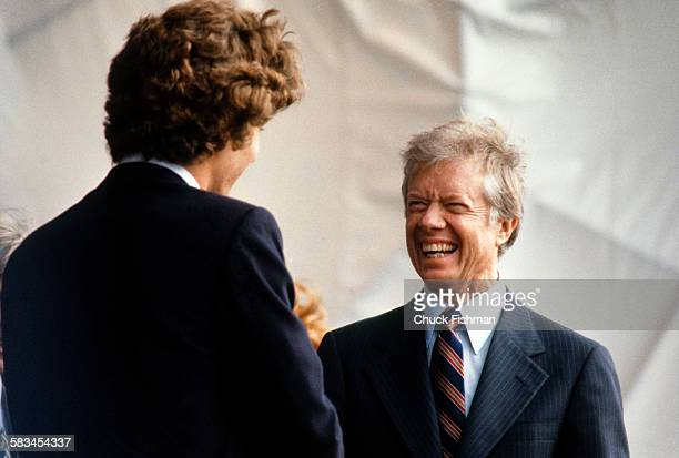 American President Jimmy Carter smiles while speaking with John F Kennedy Jr at the dedication ceremony for the John F Kennedy Presidential Library...