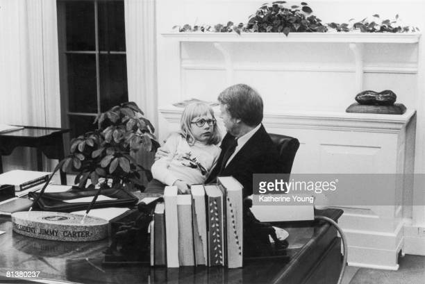 American President JImmy Carter talks with his daughter Amy who sits on his lap in the Oval Office of the White House Washington DC 1978