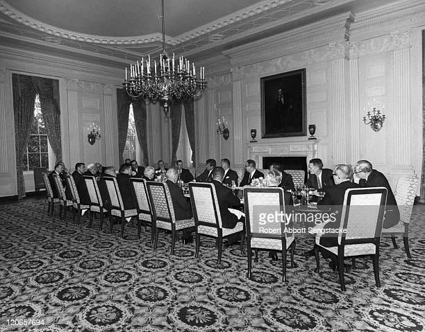 American President John F Kennedy host a dinner meeting in the White House Washington DC early 1960s Among the attendees is American newspaper...