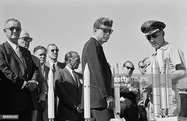 American President John F Kennedy is briefed by Director of Eastern Test Range Lt Col Dan F Thompson on a display of scale models of booster rockets...