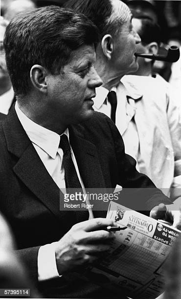 American President John F Kennedy sits in the stands a scorecard in his hand as he watches a baseball game likely at Griffith Stadium Washington DC...