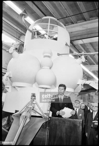 American President John F. Kennedy speaks from a lecturn in front of a full-size model of the projected design for a lunar landing module during a...
