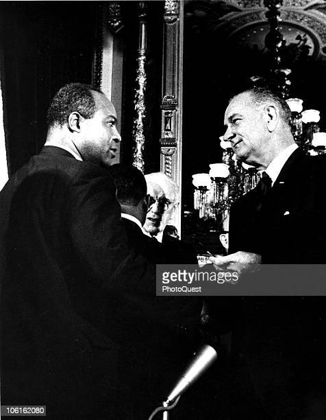 American President Lyndon B. Johnson presents one of the pens used to sign the Voting Rights Act of 1965 to the director of the Congress of Racial...