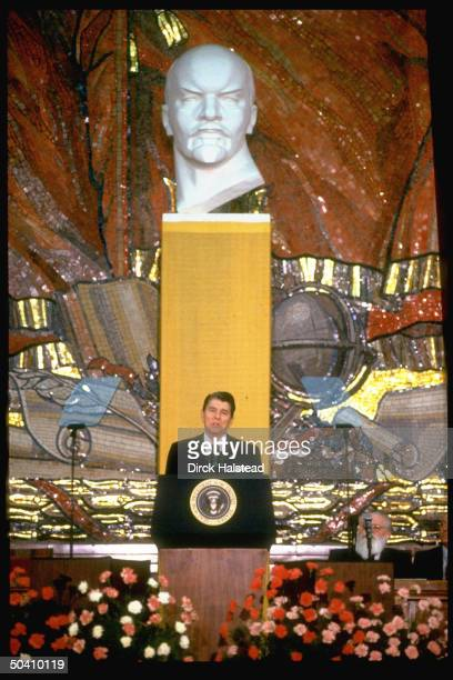 American President Reagan speaking at Moscow State University against backdrop of Lenin bust and mosaic featuring hammer and sickle during summit May...