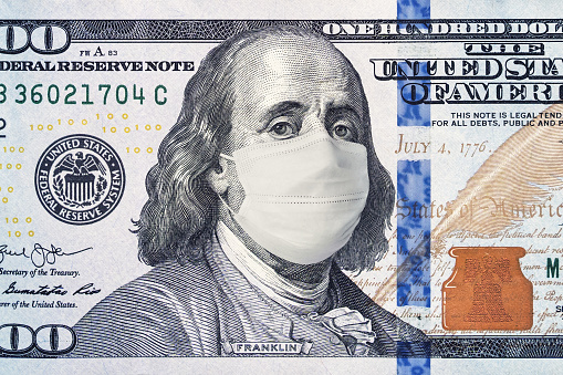 American President with face mask against CoV infection. 100 dollar banknote. Coronavirus in United States. Concept quarantine and recession. Global economy hit by corona virus outbreak and pandemic 1210689410