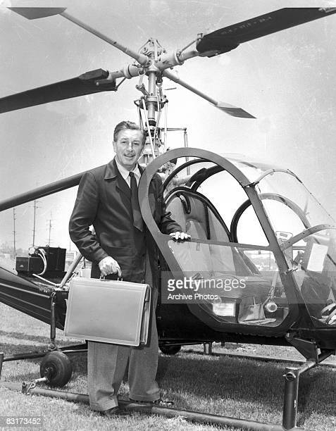 American producer director and animator Walt Disney prepares to board a helicopter bound for his theme park Disneyland under construction in Anaheim...