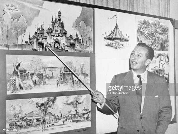 American producer director and animator Walt Disney uses a baton to point to sketches of Disneyland 1955