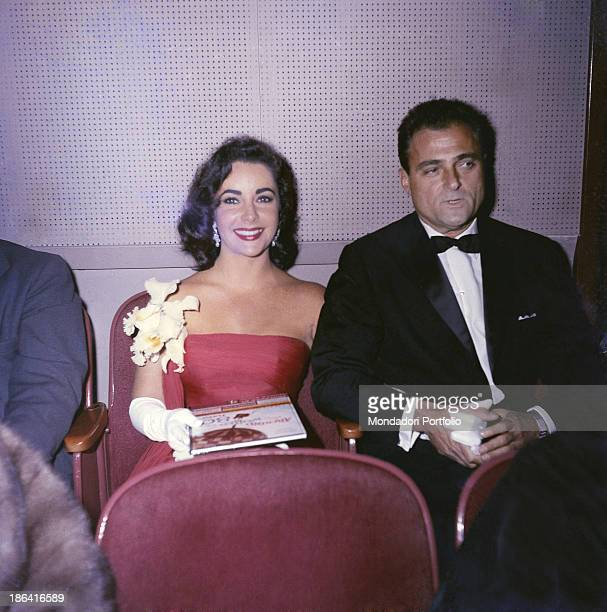 American producer Mike Todd holding the hand of her wife Britishborn American actress Elizabeth Taylor during the presentation of the film Around the...