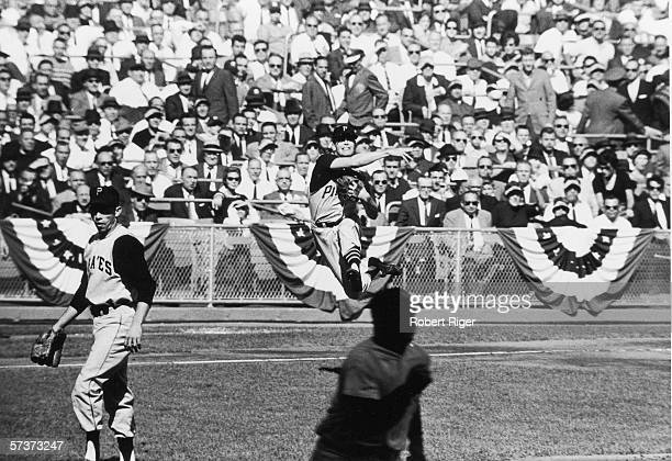 American professional baseball player Don Hoak third baseman for the Pittsburgh Pirates jumps in the air and throws the ball to first base during the...