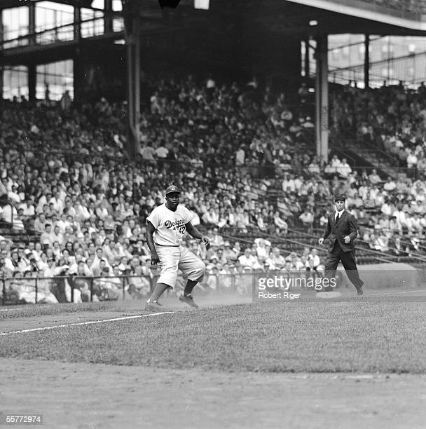American professional baseball player Jackie Robinson of the Brooklyn Dodgers takes a huge lead off third base during a game at Ebbets Fields,...
