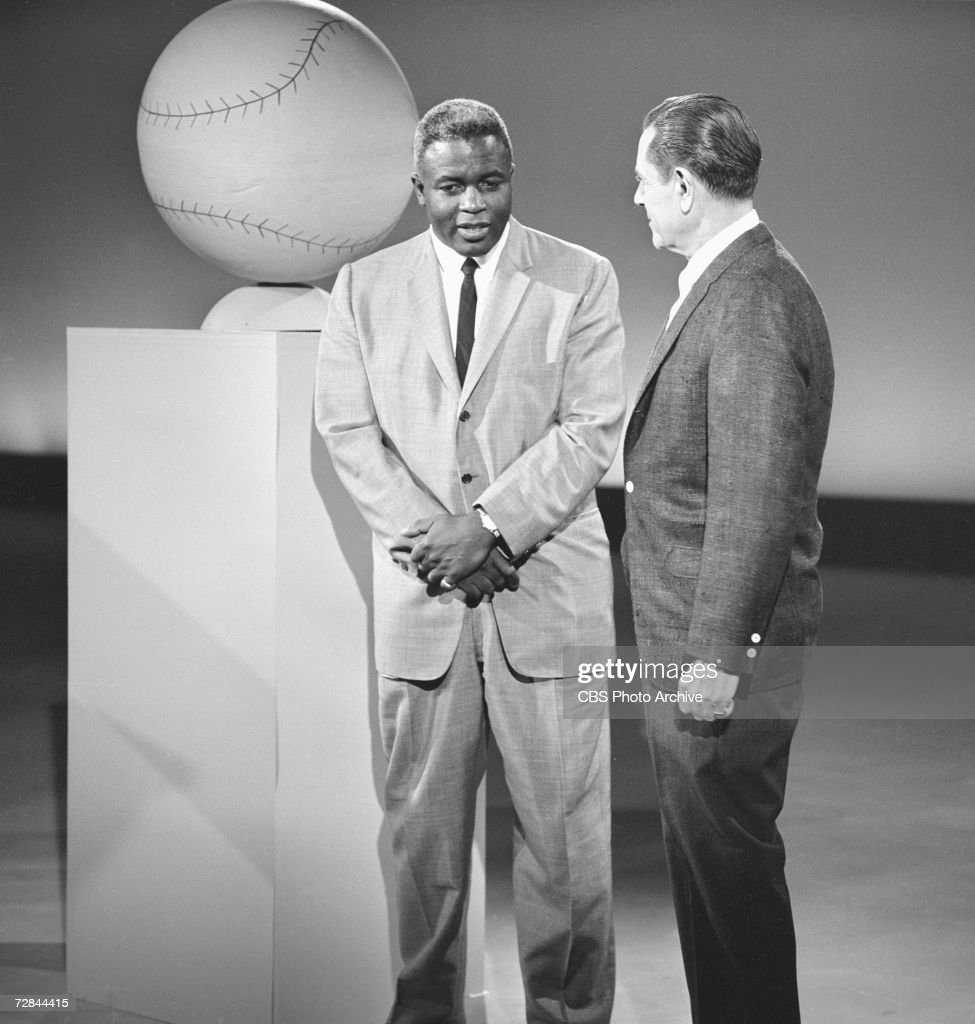 American professional baseball player Jackie Robinson (1919 - 1972) (left), who famously broke the Major League Baseball color barrier in 1947, appears next to a giant baseball on a pedestal on the CBS television program 'Who in the World' with host Warren Hull (1901 - 1974) shortly after his induction into the Baseball Hall of Fame, July 27, 1962.