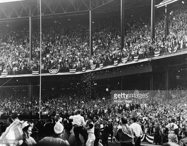 American professional baseball player Johnny Blanchard of the New York Yankees walks off the field as the crowd rushes onto the field to celebrate...