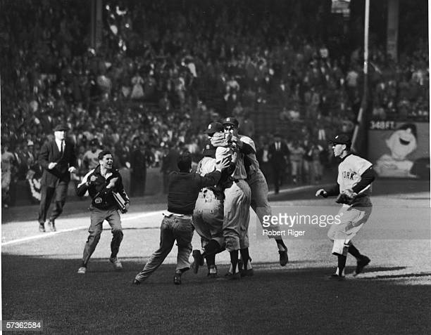 American professional baseball player Johnny Kucks pitcher of the New York Yankees celebrates with teammates and batboys who hug him after winning...