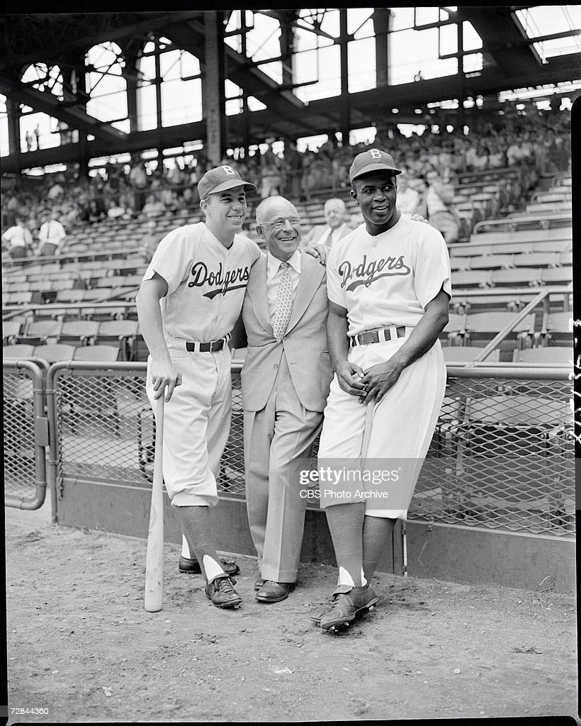 American professional baseball players Pee Wee Reese (1918 - 1999) (left) and Jackie Robinson (1919 - 1972) (right), who famously broke the Major League Baseball color barrier in 1947, pose for a photograph with Columbia Records president Edward Wallerstein (1891 - 1970) at Ebbets Field before a game, Brooklyn, New York, August 23, 1949.