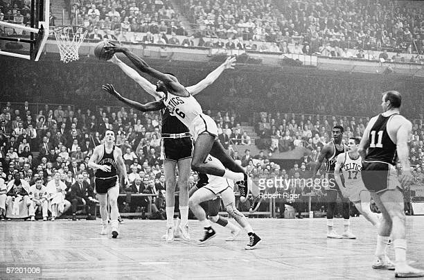 American professional basketball player Bill Russell of the Boston Celtics leaps with the ball towards the net as he bounds past the defenses of the...