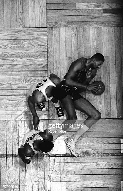American professional basketball player Wilt Chamberlain of the Philadelphia 76ers lies on the parquet floor of the Boston Garden with the ball...