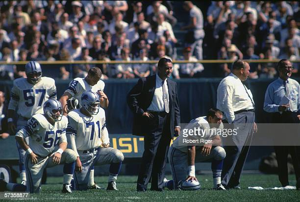 American professional football coach George Wilson stands amid other members of the support staff and their Detroit Lions players including Joe...
